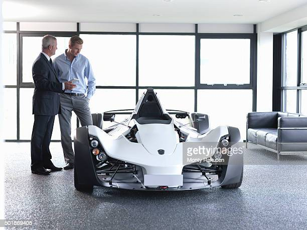 Sales person showing customer supercar in show room