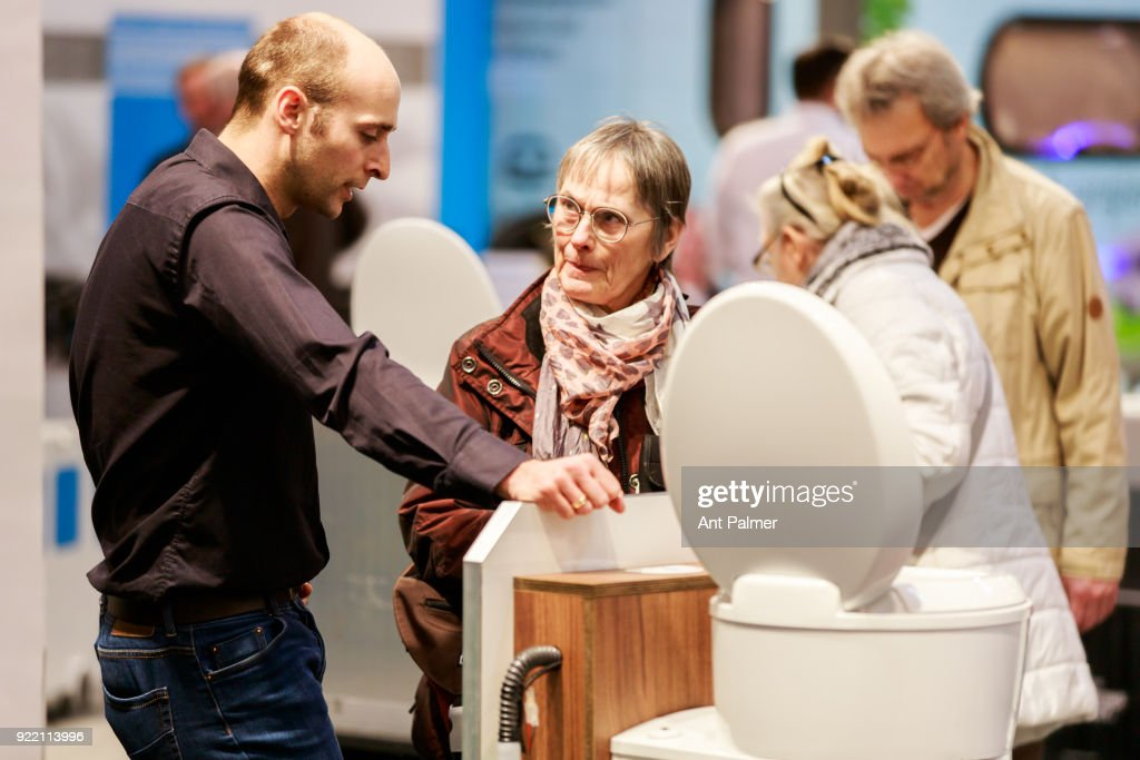 A sales representative demonstrates a portable toilet to a potential customer at the Reise + Camping Exhibition on February 21, 2018 in Essen, Germany. The annual event features over 1000 exhibitors from over 20 countries.