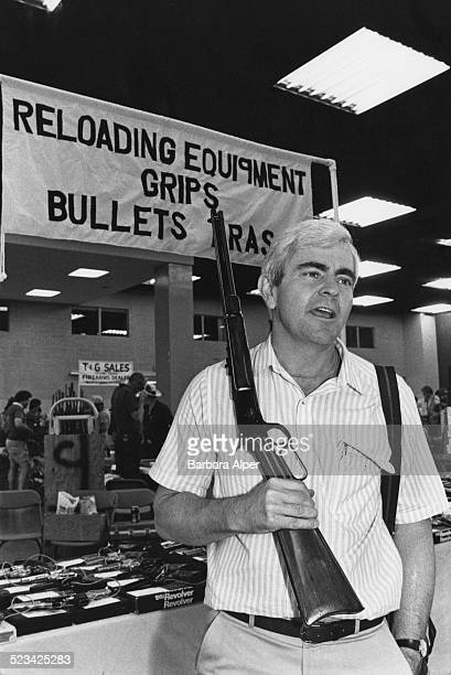 A sales representative stands next to his stall at the Original Fort Worth Gun Show Fort Worth Texas USA May 1987