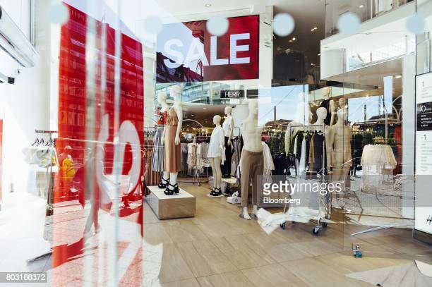 Sales signs hang on display inside a Hennes Mauritz AB fashion store in Stockholm Sweden on Wednesday June 28 2017 Costcontrol is the new watchword...
