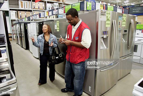 Sales specialist Rell Spevens left helps customer Carla Crump look at refrigerators at Lowe's store in Raleigh North Carolina US on Friday Nov 6 2009...