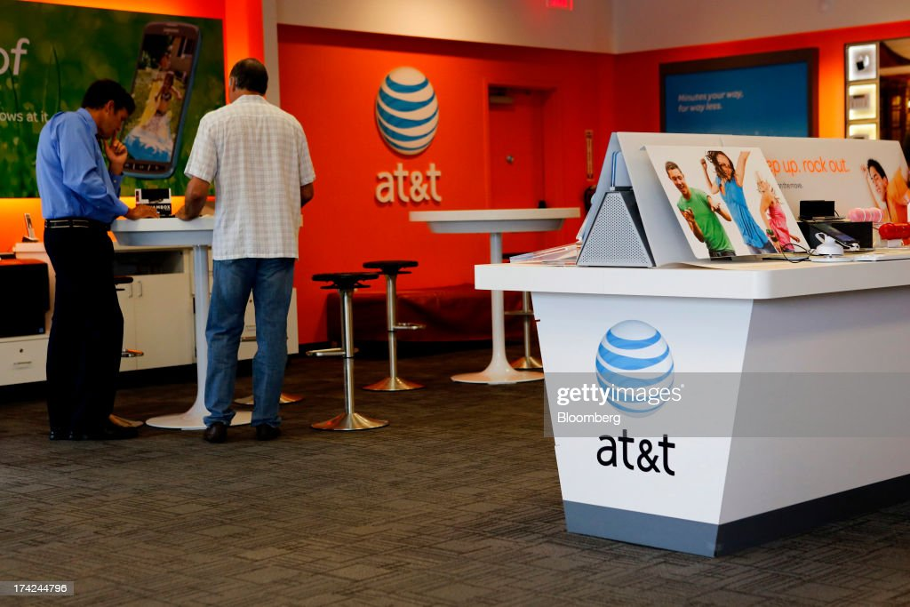 Sales staff help customers at an AT&T Inc. store in Manhattan Beach, California, U.S., on Monday, July 22, 2013. AT&T Inc. is scheduled to release earnings figures on July 23. Photographer: Patrick T. Fallon/Bloomberg via Getty Images