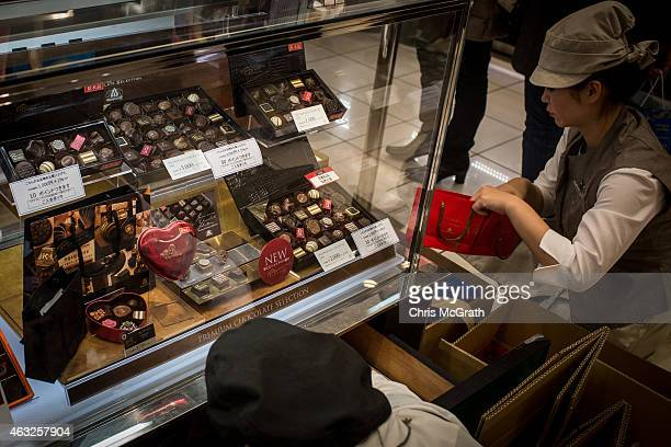 Sales staff restock valentines day gift boxes at a chocolate store in a department store on February 12 2015 in Tokyo Japan In Japan Valentine's day...