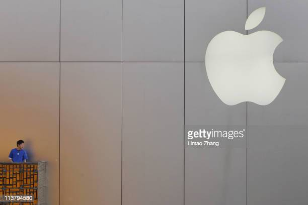 A sales staff watches people wait in line to buy the newly released Apple Inc iPad 2 tablet computer at the Apple store on May 6 2011 in Beijing...