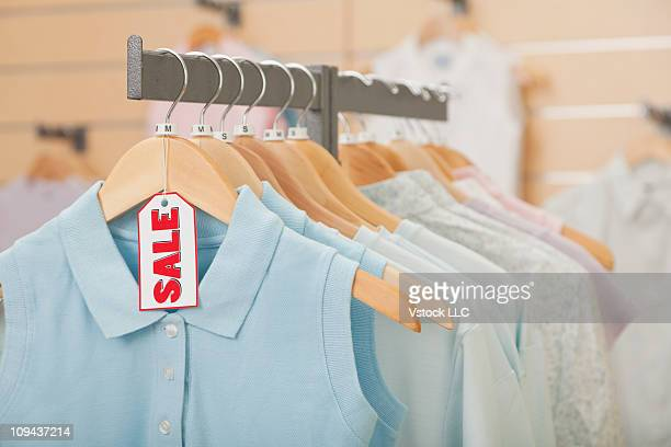 Sales tag on clothing hanging on rail in shop