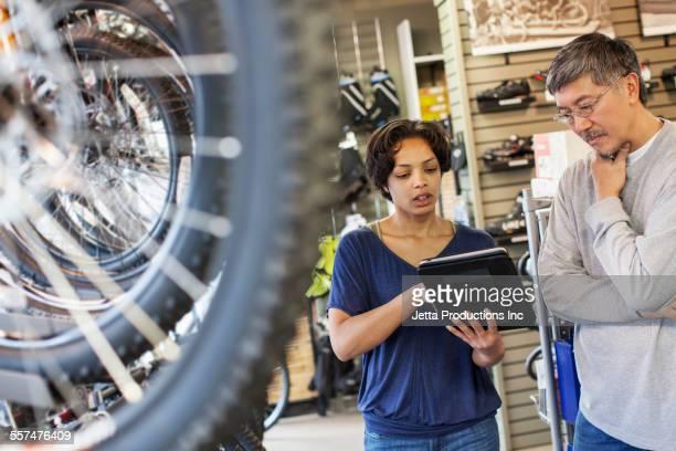 Sales team using digital tablet in bicycle shop
