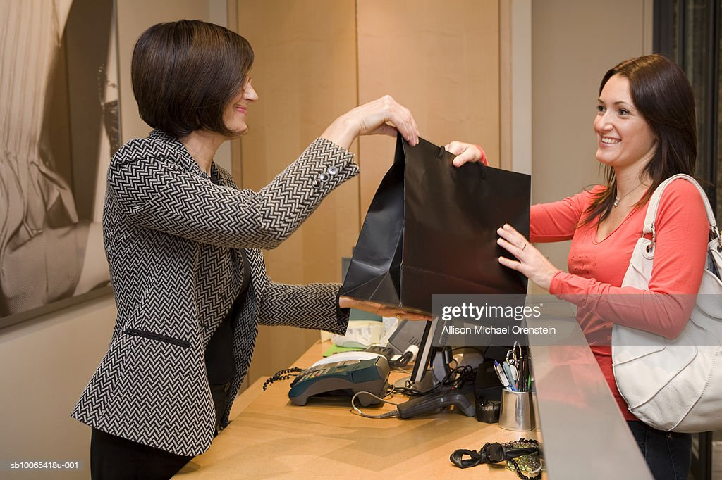 Sales woman giving customer items over counter, side view : Foto stock