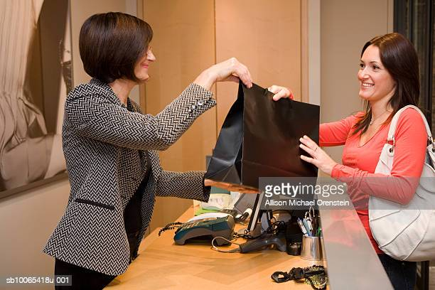 Sales woman giving customer items over counter, side view