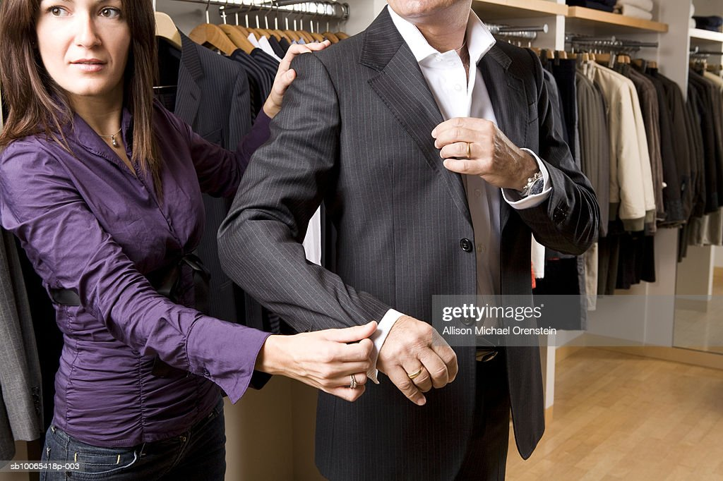 Sales woman helping customer in clothing store with suit : Foto stock