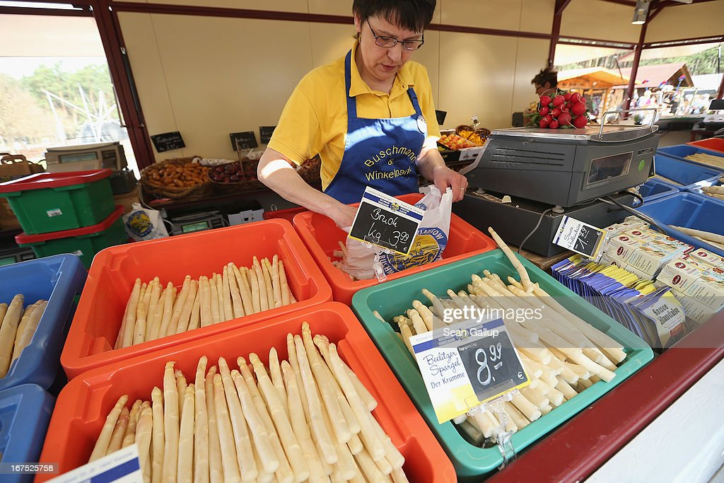 A sales woman sells freshly-harvested white asparagus at the Buschmann und Winkelmann Spargelhof Klaistow asparagus farm on April 26, 2013 near Klaistow, Germany. White asparagus, which is grown under black sheeting to protect it from the sun in order to maintain the white color, is a national delicacy and one of the main agricultural products of the local Beelitz region.