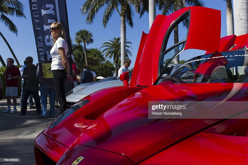 A sales woman stands next to a new Ferrari Enzo automobile for sale at the annual Cavallino Auto Competition, January 26, 2013 held at The Breakers Hotel in Palm Beach, Florida.