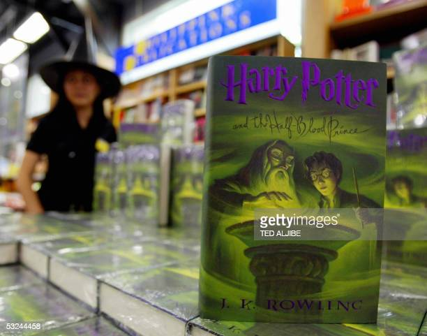 A sales woman stands next to copies of Harry Potter and the HalfBlood Prince the sixth book of the Harry Potter series by British author J K Rowling...