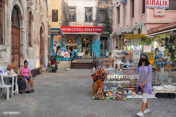 sales woman with mask and ladies sitting in the street in çeşme on a summer day. - emreturanphoto stock pictures, royalty-free photos & images