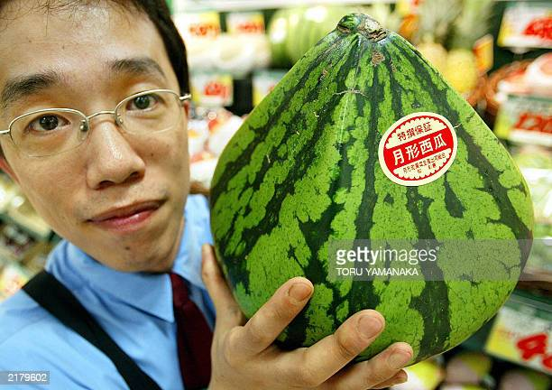 A salesclerk from Matsuzakaya department store shows off a pyramidshaped watermelon in the Ginza shopping district of Tokyo 20 July 2003 The...