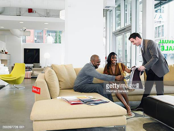 salesclerk showing fabric samples to man and woman in furniture store - furniture stock pictures, royalty-free photos & images
