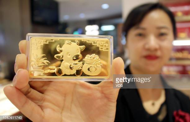 Salesclerk shows a commemorative gold bar for the upcoming Year of the Ox at a jewelry shop on October 27, 2020 in Suzhou, Jiangsu Province of China.