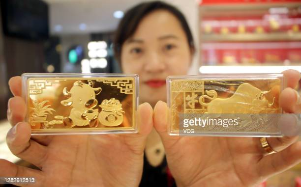 Salesclerk shows commemorative gold bars for the upcoming Year of the Ox at a jewelry shop on October 27, 2020 in Suzhou, Jiangsu Province of China.
