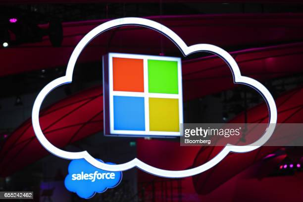 A SalesforceCom Inc left and a Microsoft Corp logo center hang beside an illuminated icloud icon at the CeBIT 2017 tech fair in Hannover Germany on...