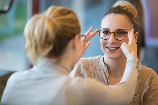 Salesgirl Assisting Customer To In Wearing Glasses 526734122