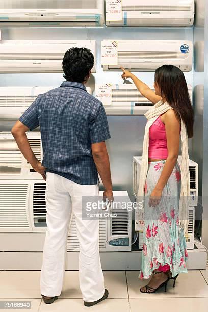 Salesgirl showing air conditioner to man in supermarket