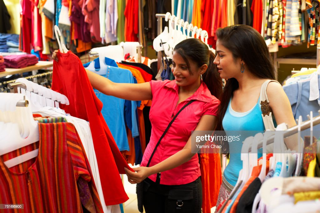 Salesgirl showing dress to woman in supermarket : Stock Photo