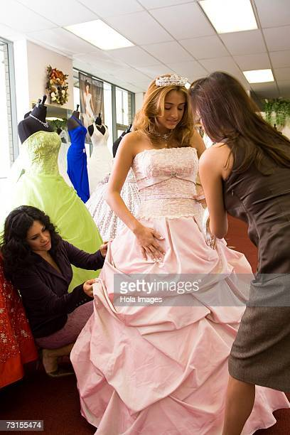 Salesgirl taking measurements on teenage girl in party dress