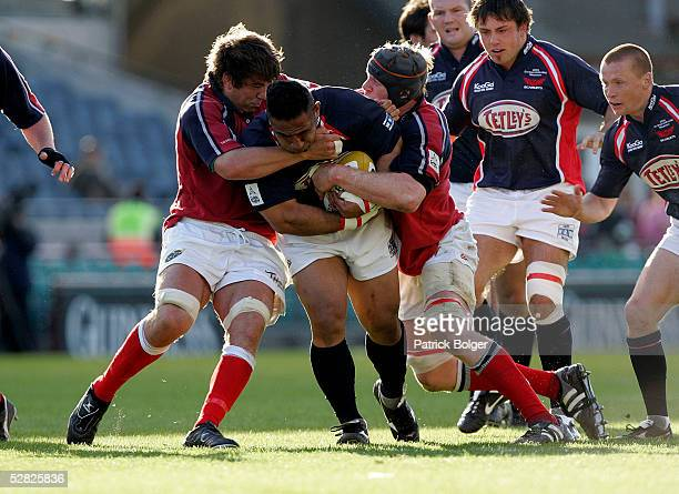Salesi Finau of Llanelli is tackled by Donncha O'Callaghan and Paul O'Connell of Munster during the Celtic Cup Final between Munster and Llanelli...