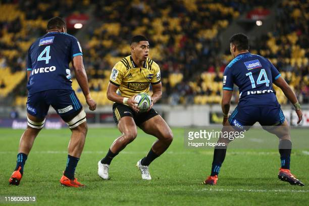 Salesi Rayasi of the Hurricanes attempts to evade Patrick Tuipulotu and Rieko Ioane of the Blues during the round 18 Super Rugby match between the...