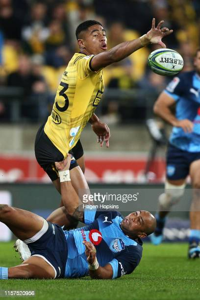Salesi Rayasi of the Hurricanes passes in the tackle of Cornal Hendricks of the Bulls during the Super Rugby Quarter Final match between the...
