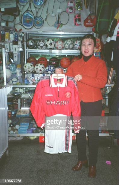 A saleslady in a Fushun sport shop shows off the strip of the Manchester United soccer team Fushun is home to the Liaoning soccer club which is...