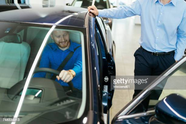 salesman advising customer in car dealership - test drive stock pictures, royalty-free photos & images
