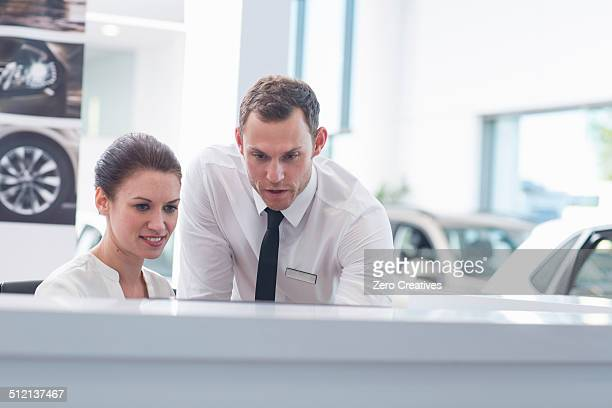 Salesman and saleswoman at desk in car dealership