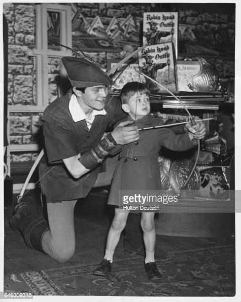 A salesman Anthony Moore dressed as Robin hood helps young David Clark with a toy bow and arrow set in the toy department at Whiteley's department...