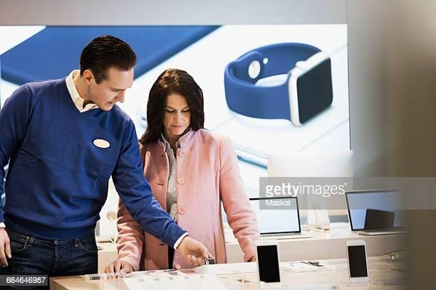 salesman assisting customer in buying smart watch at store - electronics store stockfoto's en -beelden