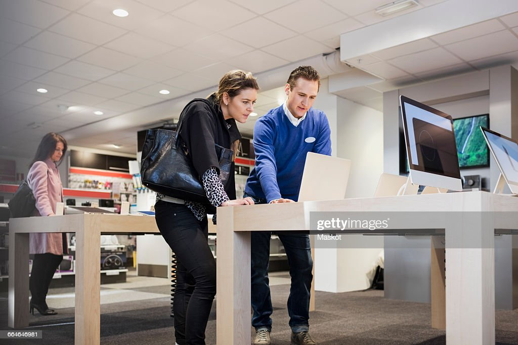 Salesman assisting female customer in buying laptop at store : Stock Photo