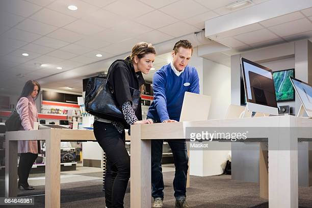 salesman assisting female customer in buying laptop at store - electronics store stock photos and pictures