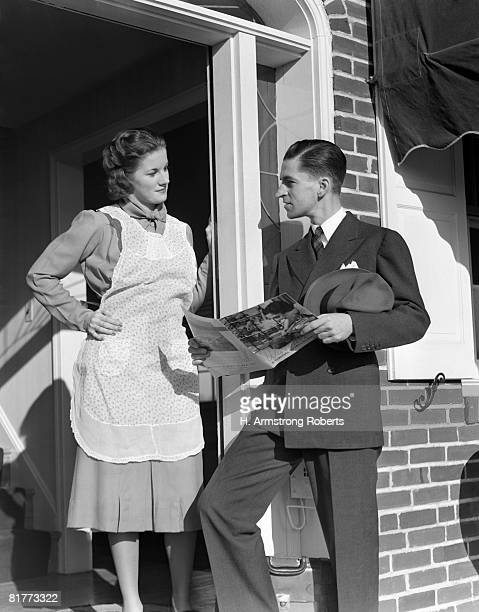 Salesman At Door Of A House Wife Showing Her A Brochure Of His Product He Is Dressed Ia A Suit She Is Wearing A White Apron Over A Dressey Dress.
