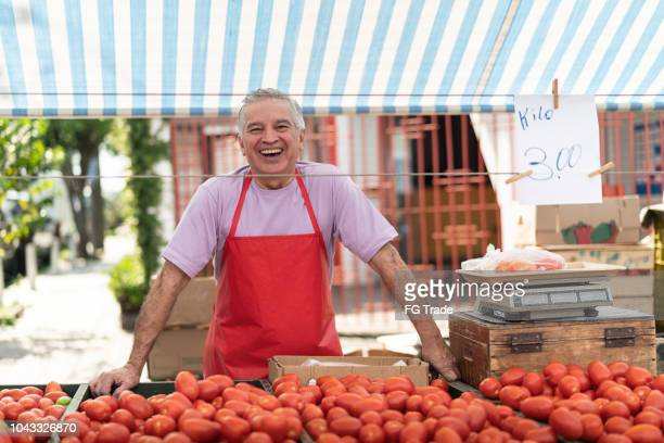 salesman at farmer's market - farmers market stock pictures, royalty-free photos & images