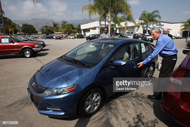 A salesman at Honda of Pasadena shows customers a newly arrived 2010 Honda Insight hybrid car on March 30 2009 in Pasadena California The redesigned...