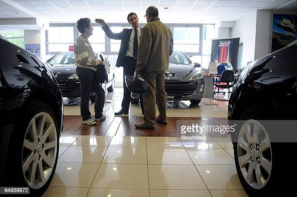 Salesman Blaise Deschamps center speaks to customers Francoise Leblouch left and Pedro Castro at a PSA Peugeot Citroen showroom in Paris France on...