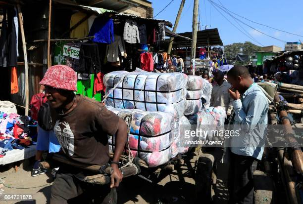 A salesman carries his second hand clothes at Gikomba market in Nairobi Kenya on April 3 2017 Kenyan government's exhortation on buying new clothes...