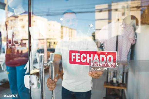 salesman closing the clothing store - closed stock pictures, royalty-free photos & images