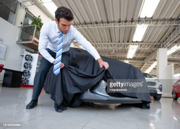 salesman disclosing a car covered with tarpaulin at the dealership - tarpaulin stock pictures, royalty-free photos & images