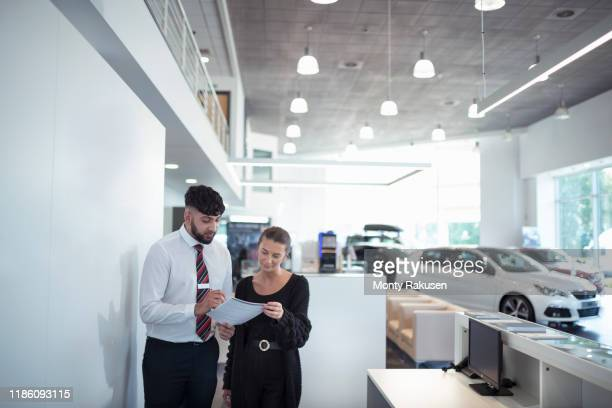 salesman discussing contract with customer in car dealership - car dealership stock pictures, royalty-free photos & images