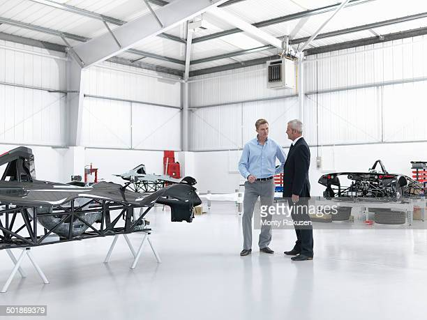 Salesman discussing supercar with customer in factory