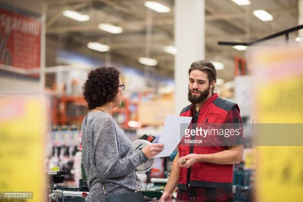 Salesman discussing with female customer holding document in hardware store