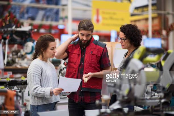 Salesman discussing with female customers in hardware store