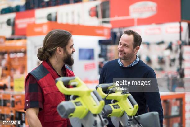 Salesman discussing with male customer in hardware store