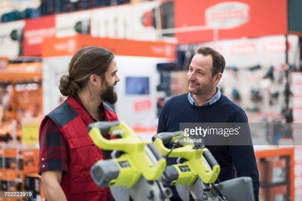 salesman discussing with male customer in hardware store - klanten georiënteerd stockfoto's en -beelden