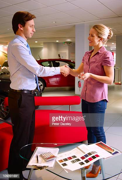 Salesman does the deal in car showroom